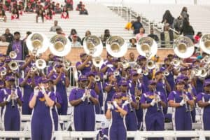 Benedict College band performing at a football game with spectators sitting in the bleachers behind them.