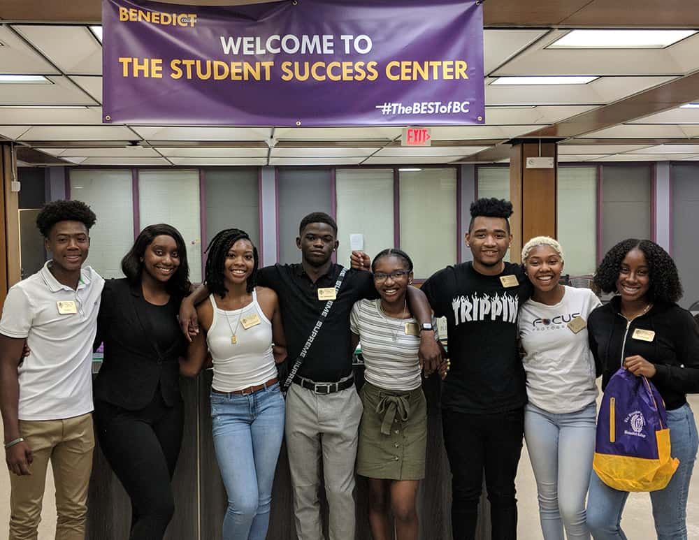 "Freshman class officers stand with their arms around each other's shoulders under a banner that reads ""Welcome to the Student Success Center."""