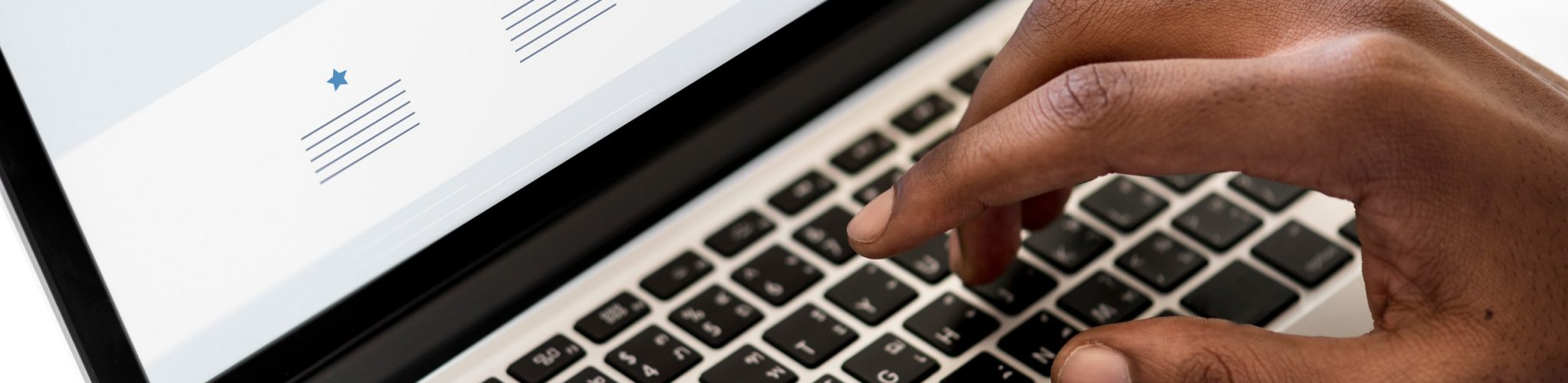 Open laptop with a hand typing on the keyboard